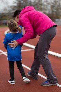 Atletiek 1 van de trainers coacht kind